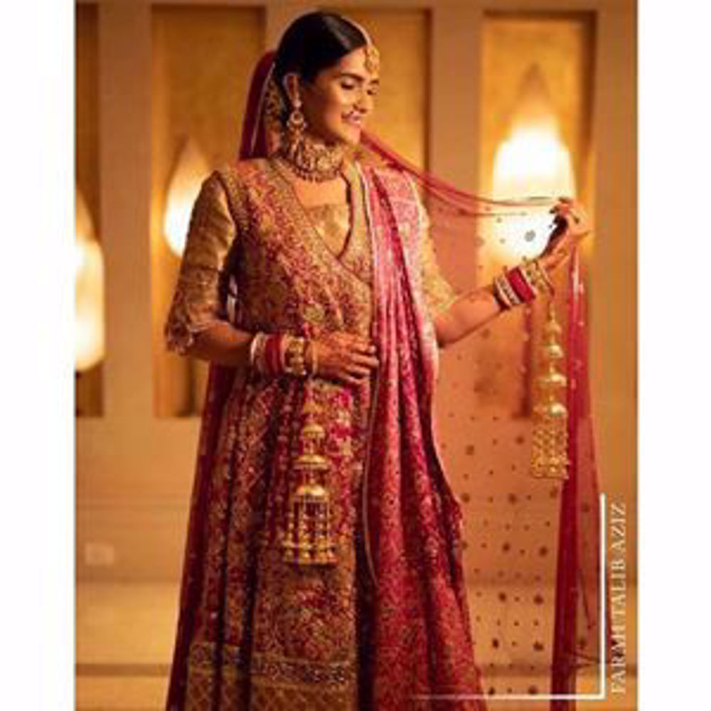 Picture of Kaneeka, gorgeous on her wedding in a bougainvillea pink and dusky gold Farah Talib Aziz signature kalidaar angarkha
