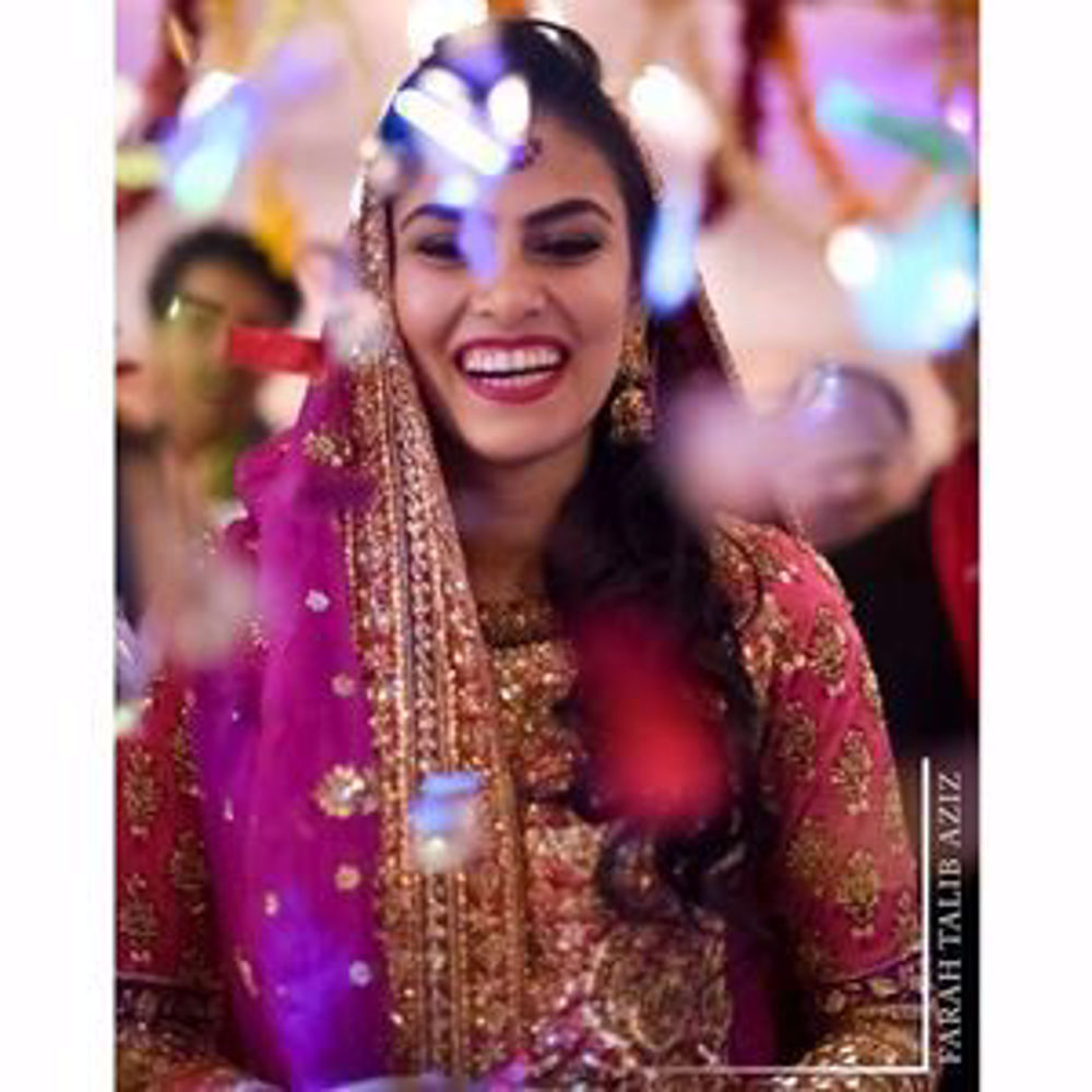 Picture of Madeeha Khan, gorgeous on her Mehndi in a burnt orange and magenta pink Farah Talib Aziz signature lengha choli