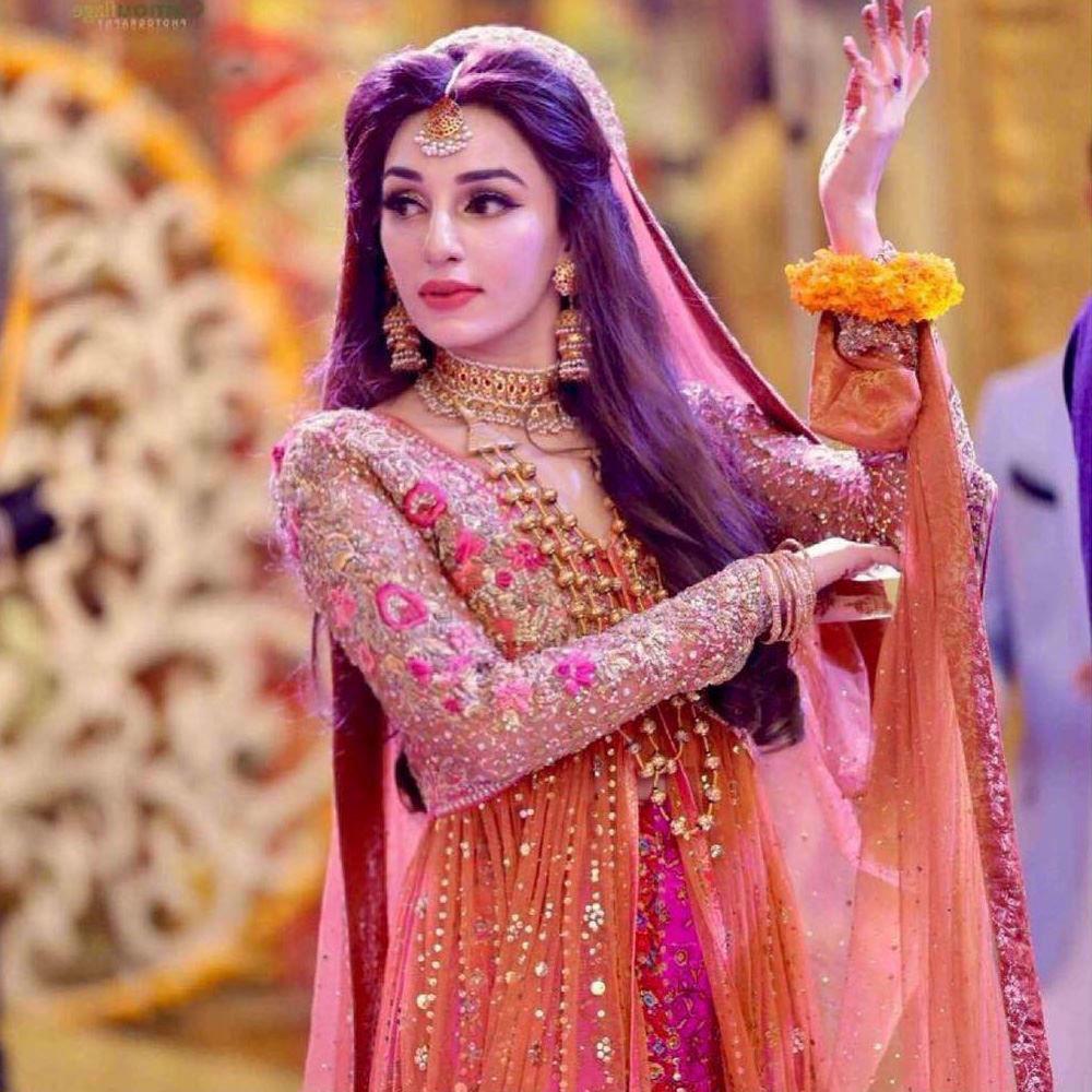 Picture of Saba Abbas Balouch, gorgeous on her Mehndi in a burnt orange and magenta pink Farah Talib Aziz kalidaar