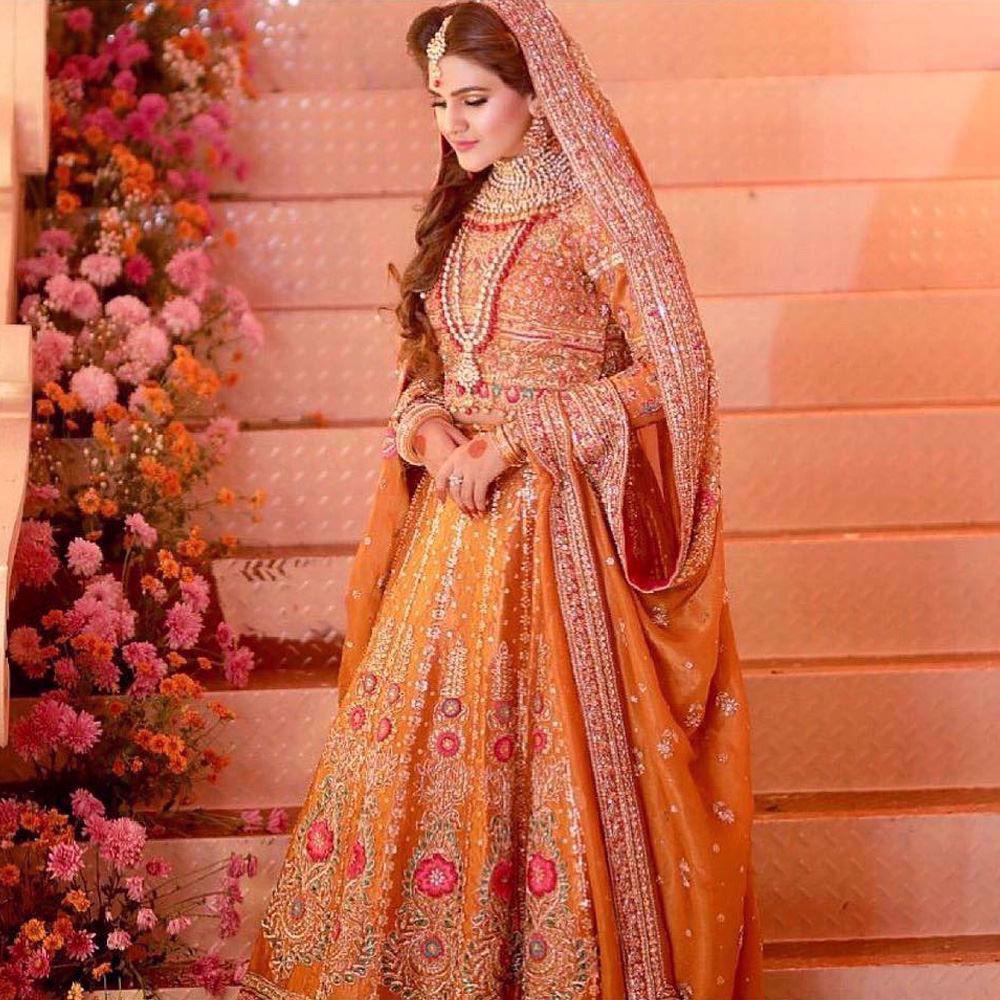 Picture of Sijjal Elahi absolutely regal in a burnt orange Farah Talib Aziz lengha choli featuring intricate gold zardozi, French knots and single dhaagha embellishments