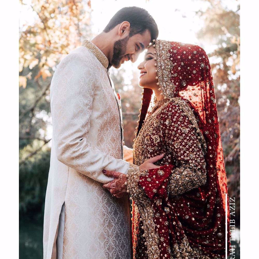 Picture of Syeda, a breathtaking traditional bride on her wedding day in a classic red and gold Farah Talib Aziz signature bridal