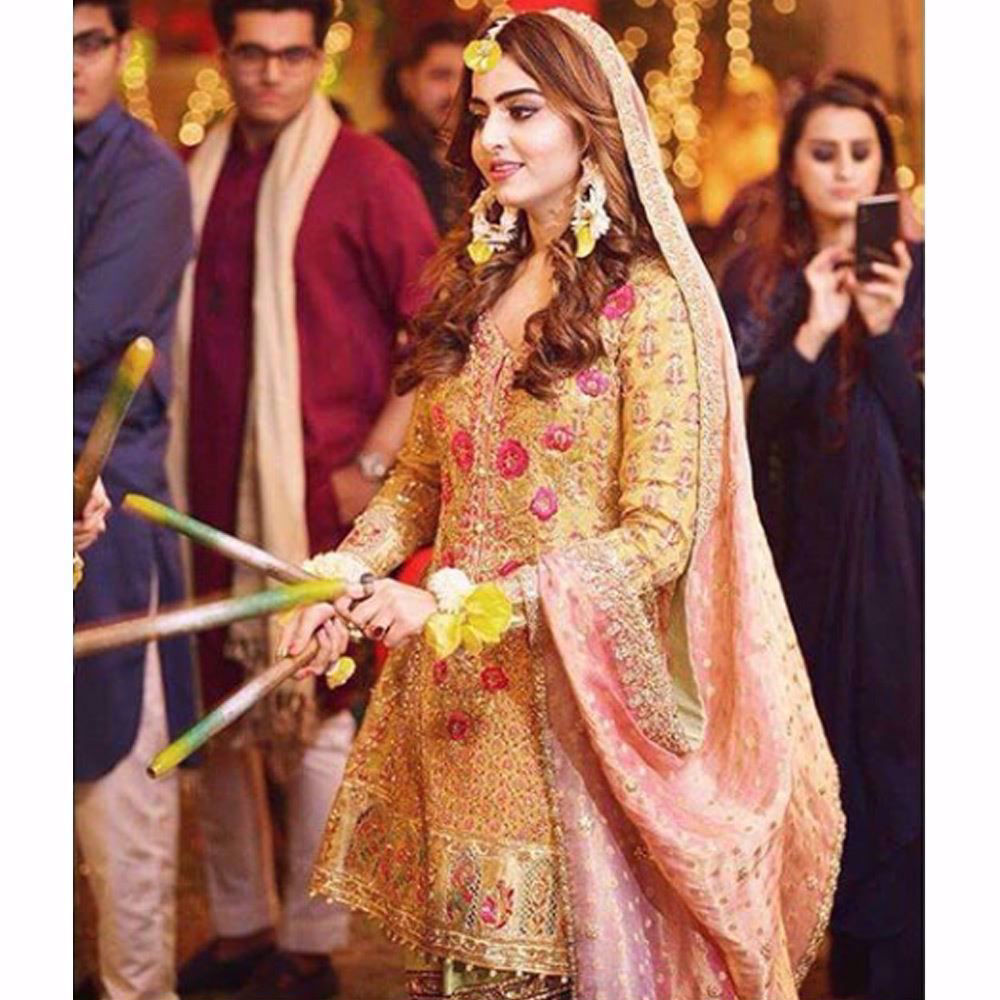 Picture of Sara, glowing in a saffron yellow kalidaar paired with a mint gharara