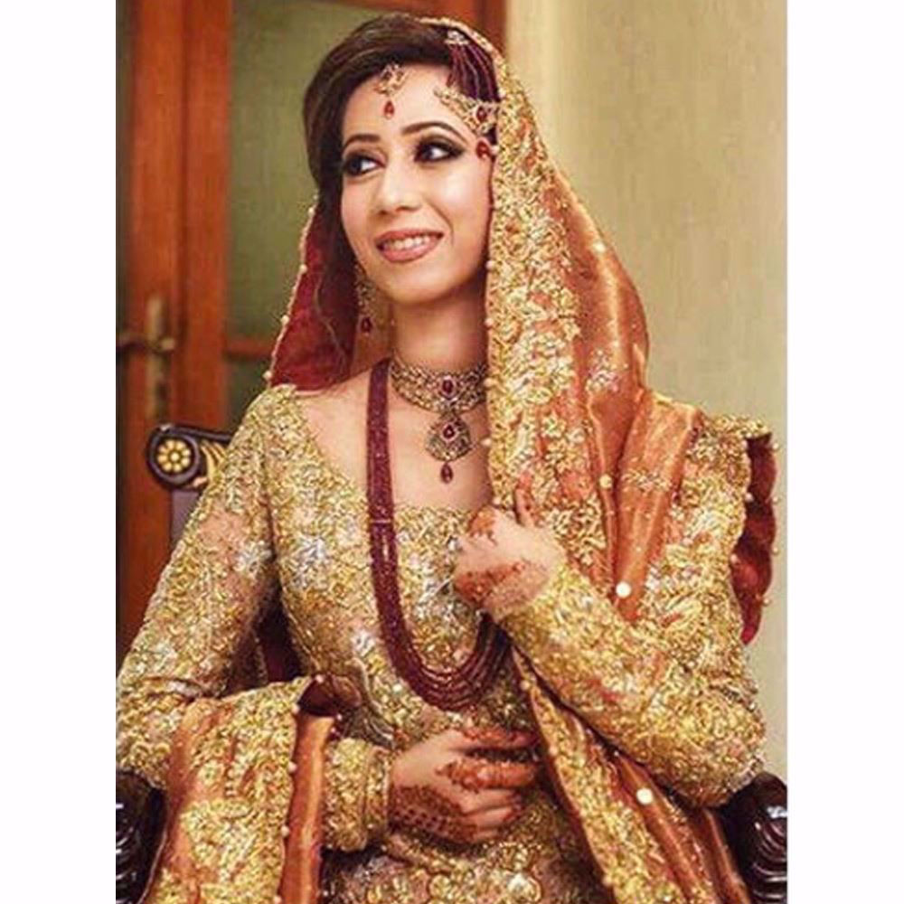 Picture of Shimmering in a regal gold and coral Farah Talib Aziz bridal with hints of bougainvillea and rose pinks