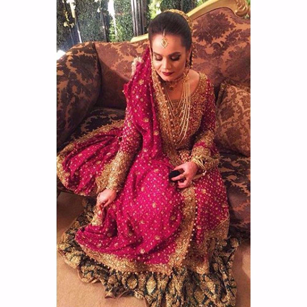 Picture of Sarah, traditionally regal in an anaar red and emerald green Farah Talib Aziz bridal