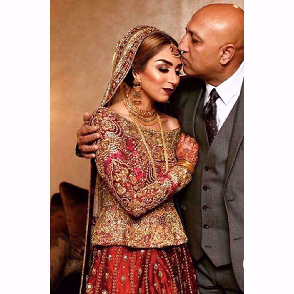Picture of Farah Talib Aziz Bride in traditional reds featuring timeless embellishments on structured silhouettes