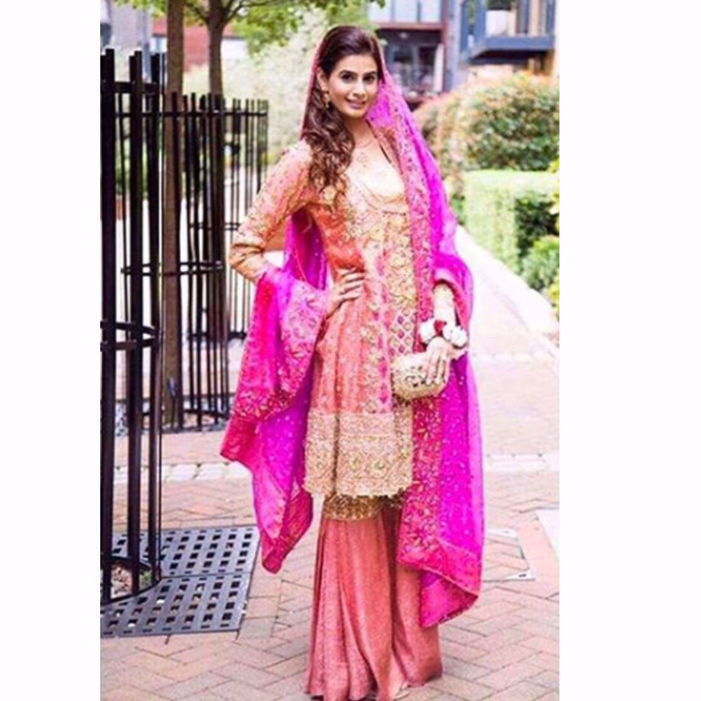 Picture of An absolute beauty on her Mehndi in a burnt orange Farah Talib Aziz kalidaar angarkha with festive bursts of pinks and greens