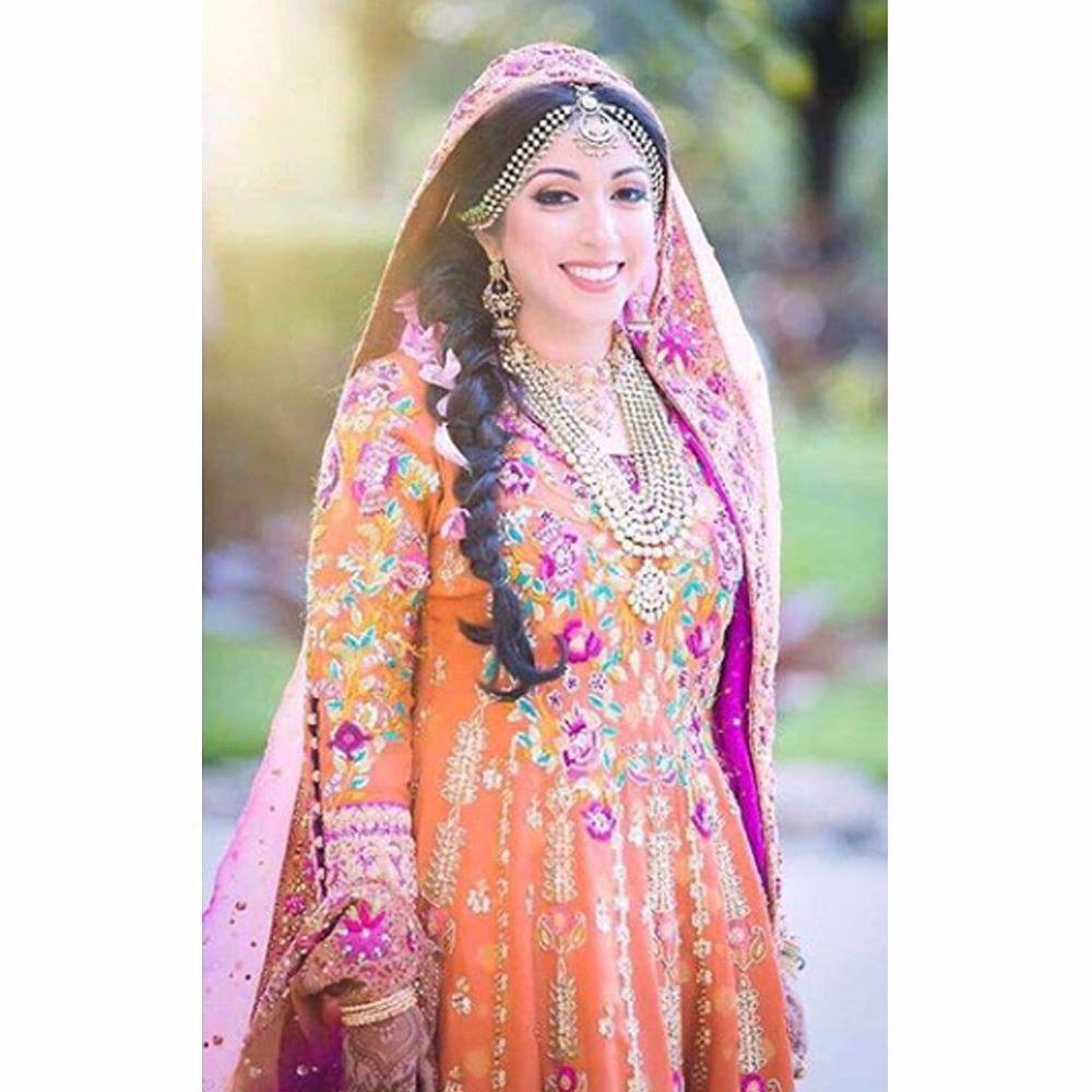Picture of Burnt orange Farah Talib Aziz kalidaar peshwas with festive bursts of pinks and greens