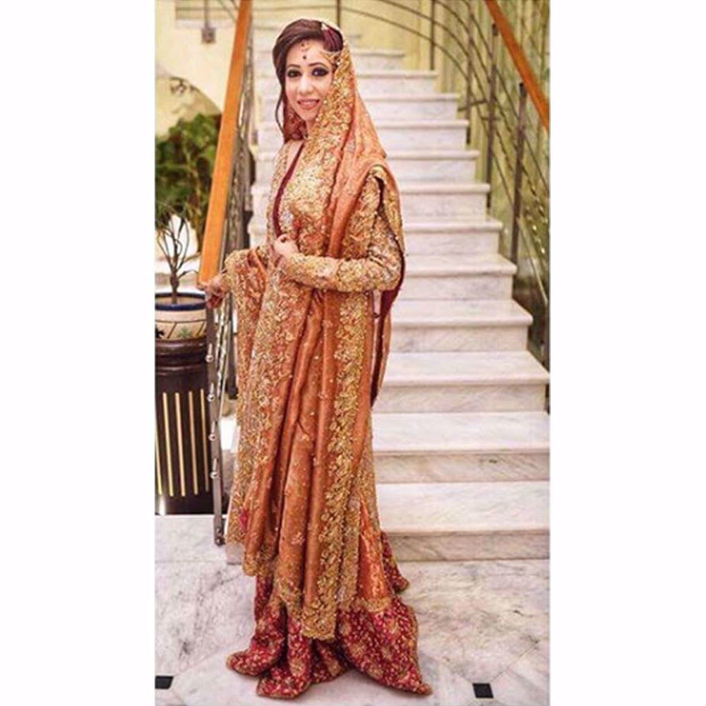 Picture of Samreen, shimmering in a regal gold and coral Farah Talib Aziz bridal with hints of bougainvillea and rose pinks