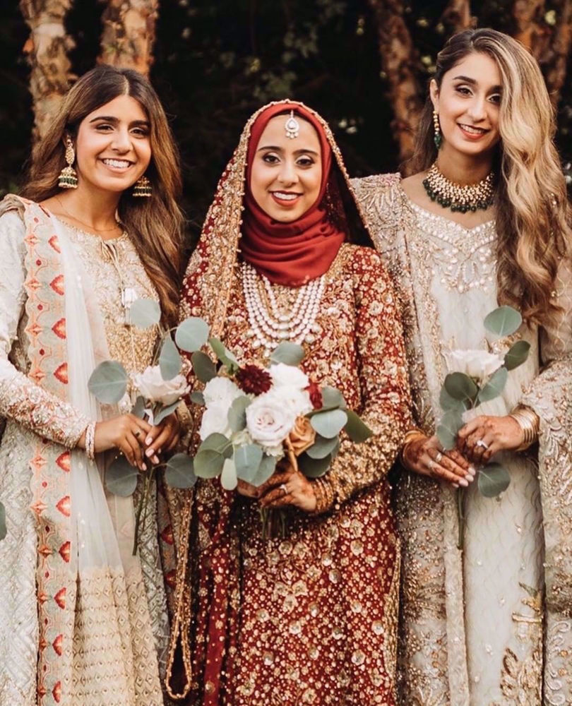 Picture of Marriyah Simjee, resplendent at her wedding in traditional shades of reds featuring intricate embellishments in gorgeous, glistening golds