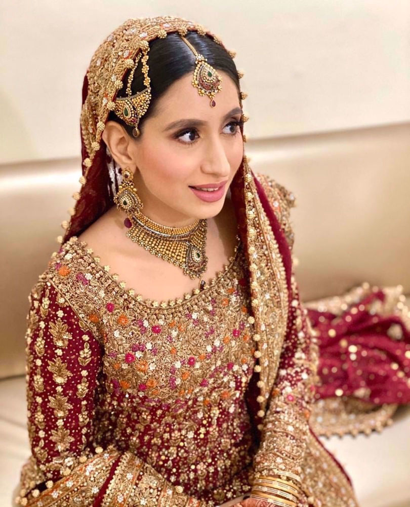 Picture of Sana Humayun wears a traditional #FarahTalibAziz ensemble in scarlet red with gold embellishments masterfully hand-embroidered onto the finest of fabrics to create a stunning heirloom bridal