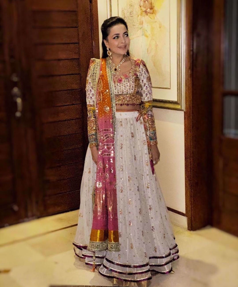 Picture of Our creative director Maliha Aziz Jamil, looks absolutely gorgeous in a stunning ivory lehnga choli accentuated with a signature #FarahTalibAziz chunri chaddar in shades of burnt orange and magenta
