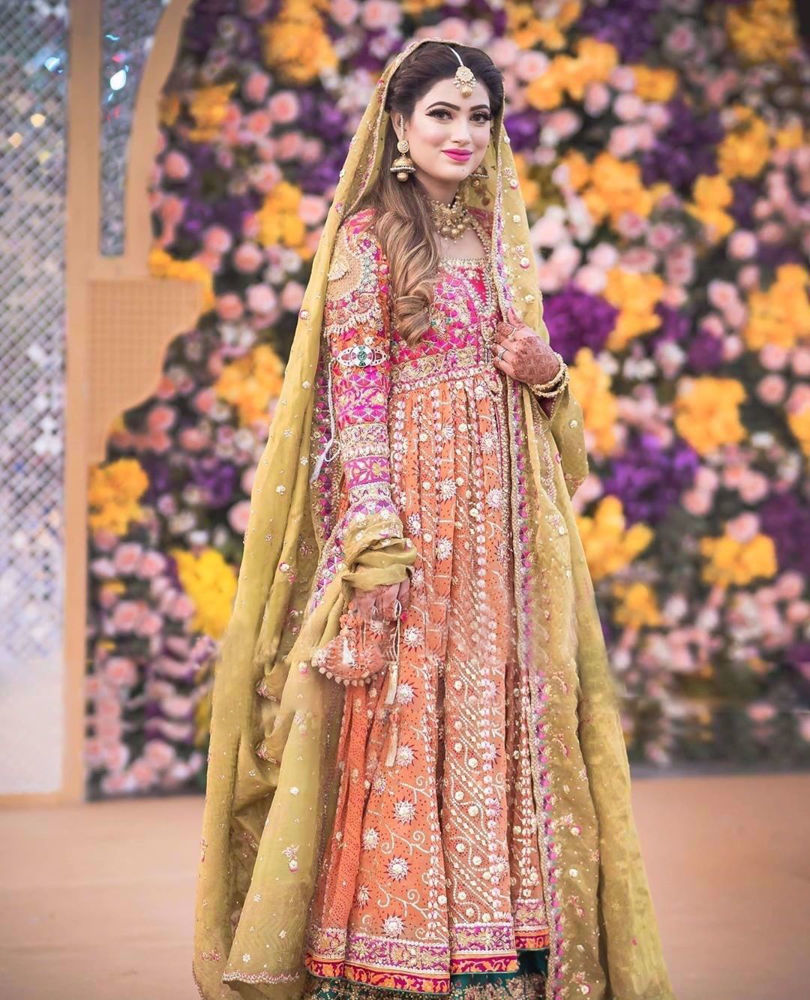 Picture of Nida Gillani at her mehndi in a signature #FarahTalibAziz ensemble. Vivid colours, intricate embroideries and tradtional silhouette, flawlessly come together to create a stunningly regal bridal look