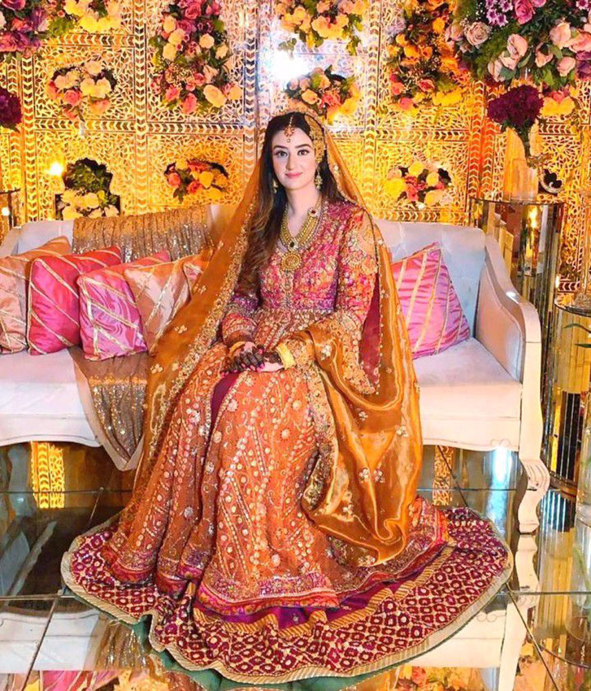 Picture of Minahil Buksh is resplendent in a signature #FarahTalibAziz kalidaar in burnt orange with a vibrant magenta lehnga, accentuated with gold embellishments and a stunning gold dupatta