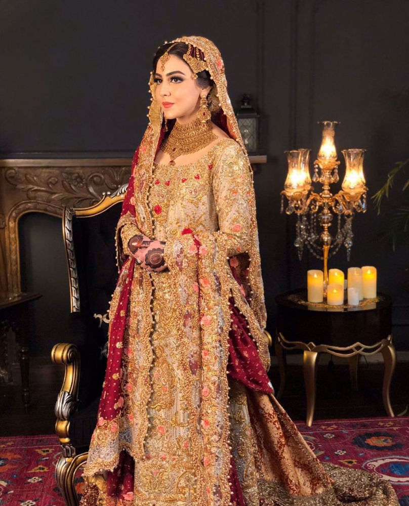 Picture of Maha looks absolutely ravishing at her wedding in a signature #FarahTalibAziz ensemble. A gold kameez offset with a scarlet dupatta, accentuated with gold embellishments and threadwork in shades of peach and scarlet