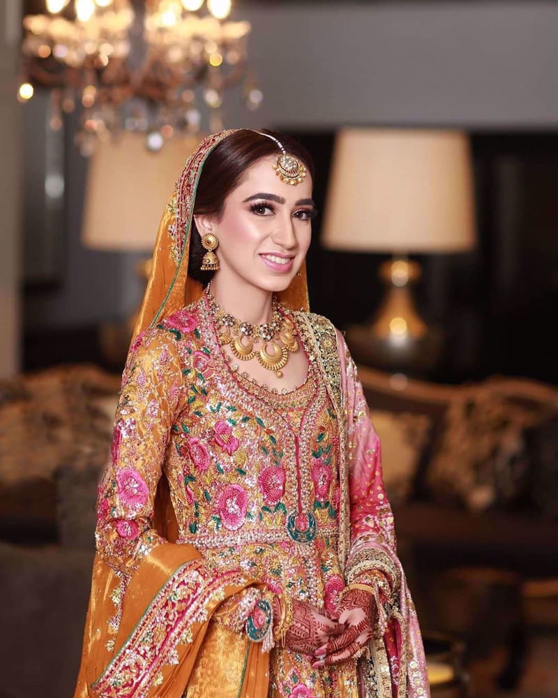 Picture of Jannat at her mehdni wearing a traditonal #FarahTalibAziz kalidaar in riot of colours and fine fabrics accentuated with gold embellishments and threadwork in shades of bougainvillea pink