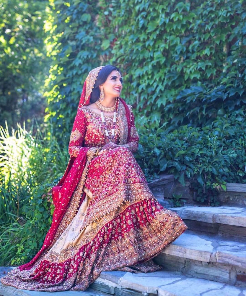Picture of Farah Talib Aziz gives us a masterclass on how to carry the iconic red bridal. Featured here is a traditional scarlett red ensemble with gold embellishments
