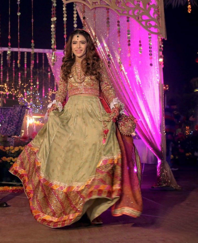 Picture of Beenish, a glowing bride in a signature #FarahTalibAziz ensemble. A refreshingly cool mint green lehnga choli, adorned with gold embroidery and thread-work