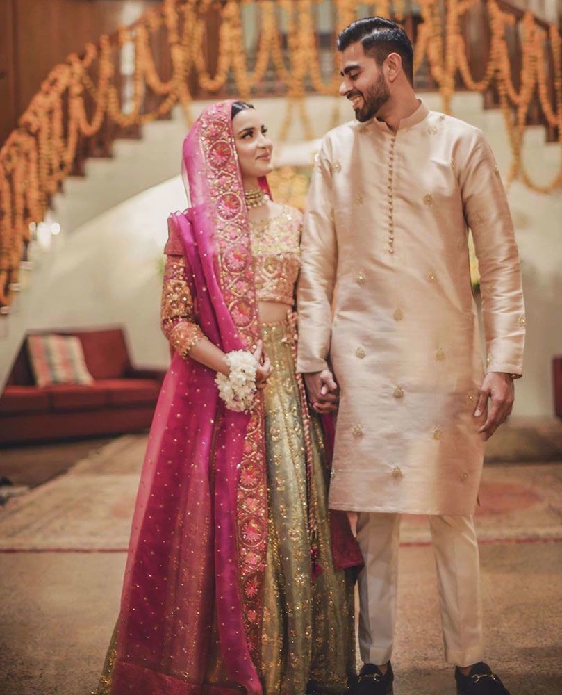 Picture of Aliya Hasnain, is beautiful at her mehndi in a striking #FarahTalibAziz ensemble. A kiwi green lehnga choli offset with a rich magenta dupatta, delicately detailed with gold embellishments and eye-catching work