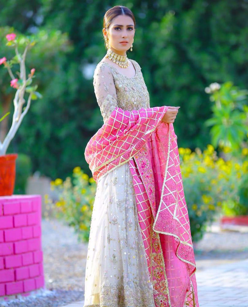 Picture of The spectacular #AyezaKhan is exquisite in a signature ivory #FarahTalibAziz kalidaar. A candy pink organza dupatta, accentuated with gold embroidery and gota provides a striking pop of color