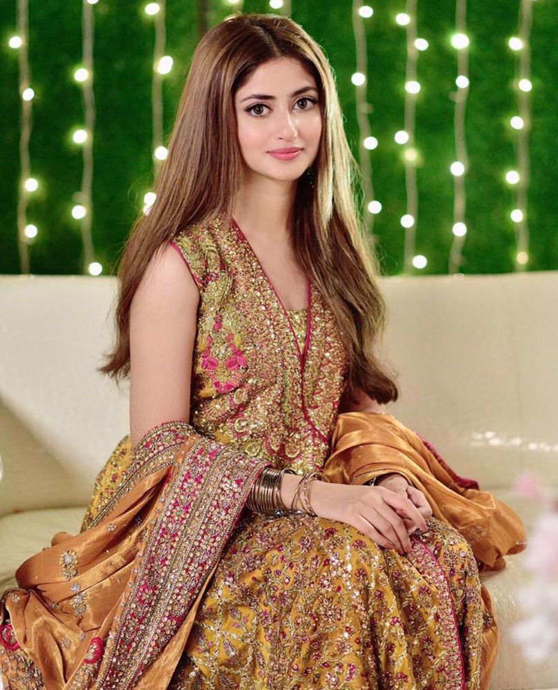 Picture of Sumptuous saffron silk, coordinating magenta pink and gold details - the #FarahTalibAziz signature kalidaar angarkha worn with effortless grace by the gorgeous Sajal Ali